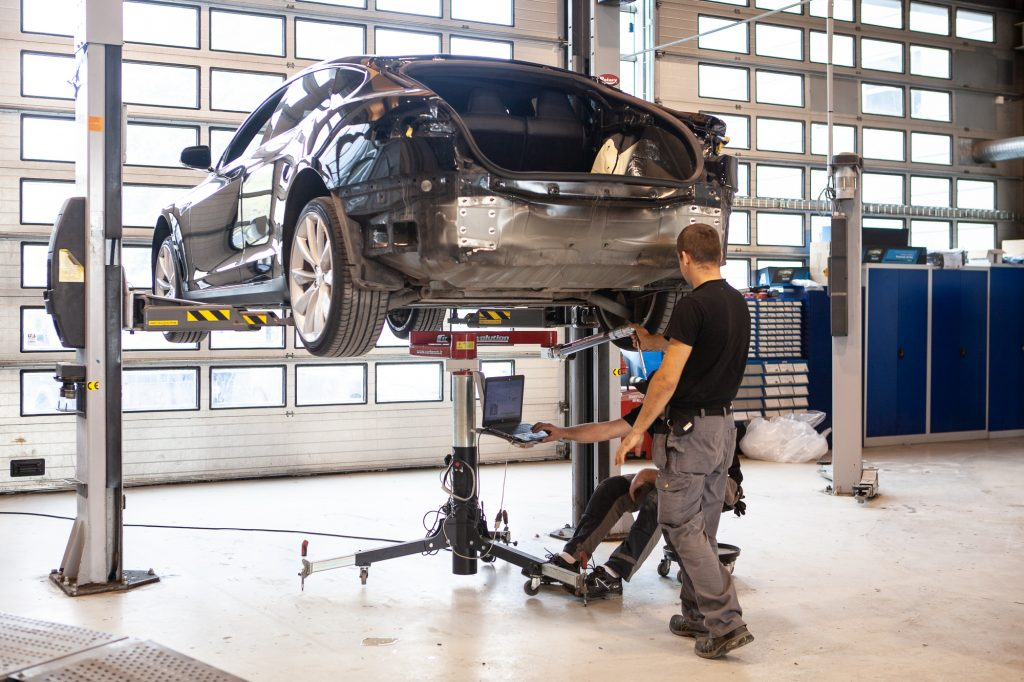 Mekanikere jobber med bil på lift